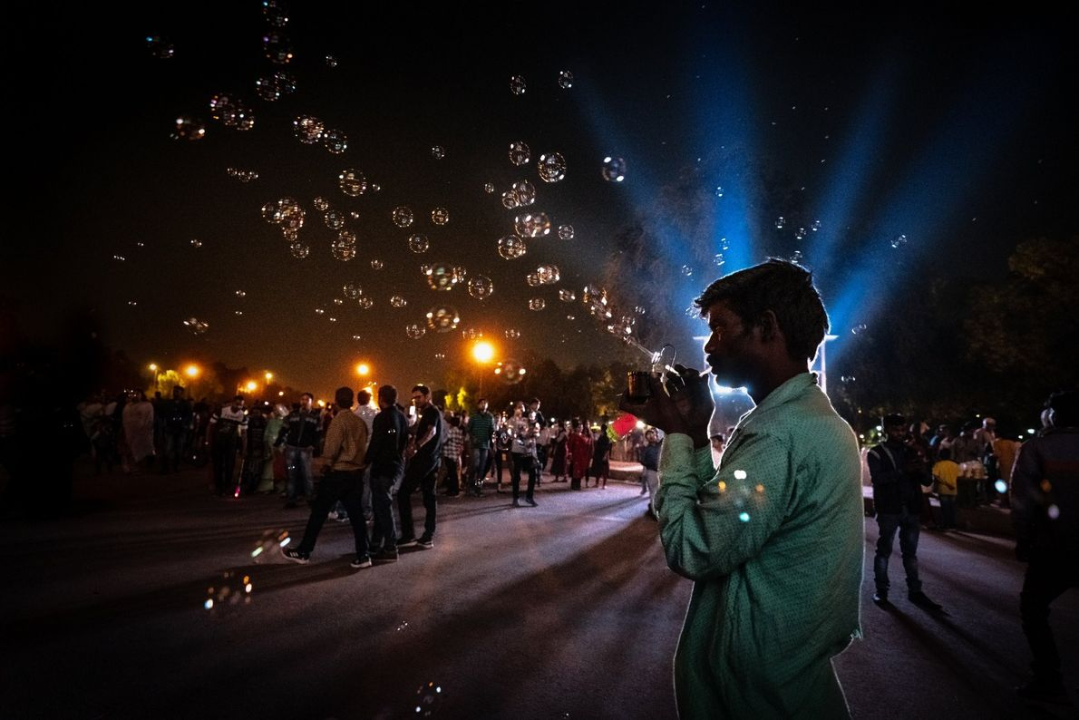 Your Shot photographer Prasanth R. documented this scene of a shopkeeper in New Delhi, India blowing ...