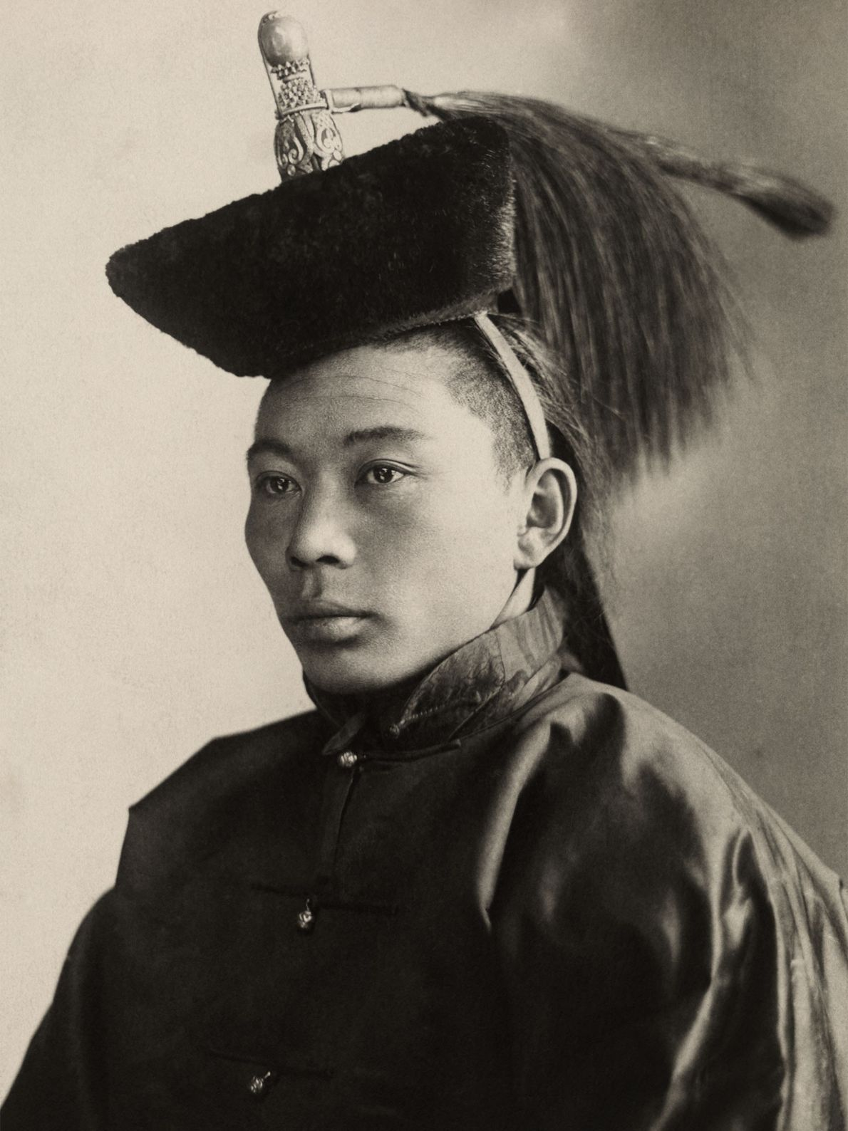 A young Mongolian prince poses for a picture, wearing a hat with embellishments that signifies his ...