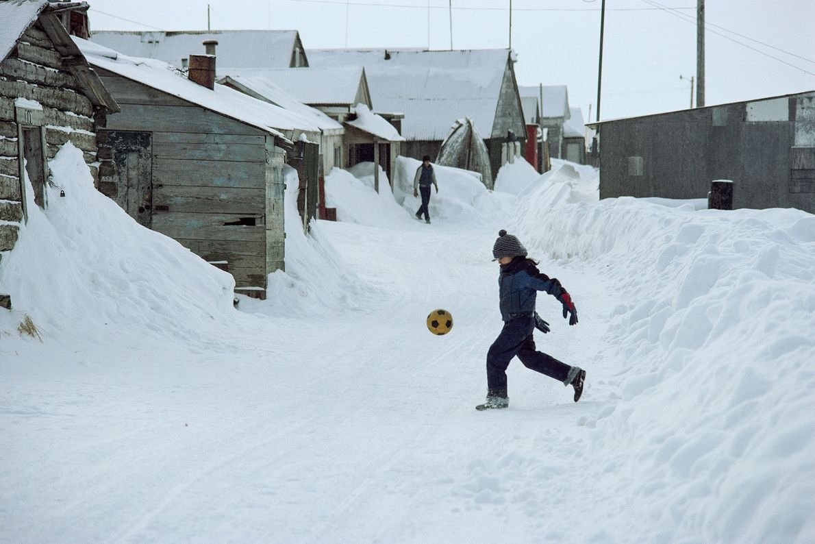A boy kicks a football on a snowy street in Barrow, Alaska.