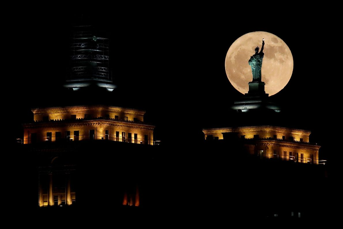 A supermoon rises in front of a replica of the Statue of Liberty sitting atop the ...