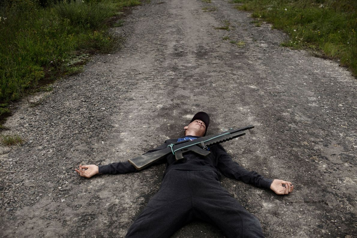 "A young Ukrainian boy lies on the ground pretending to have been killed by ""enemy fire"" ..."