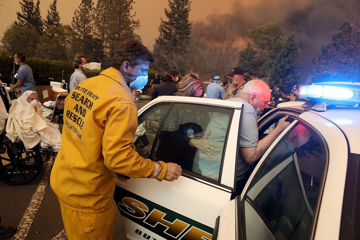 Hospital workers and first responders evacuate patients from the Feather River Hospital as the Camp Fire ...