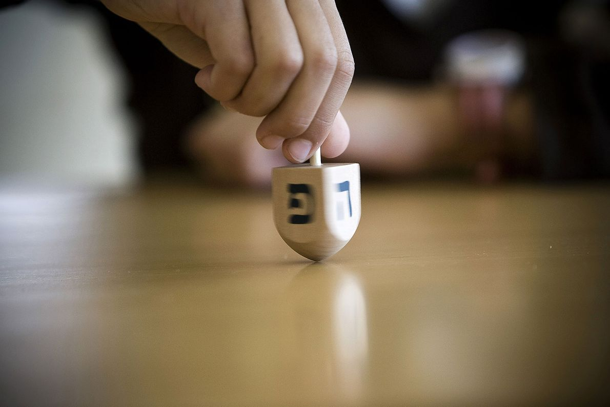Known in Hebrew as a sevivon, a four-sided dreidel ('spinning top' in Yiddish) is used in ...