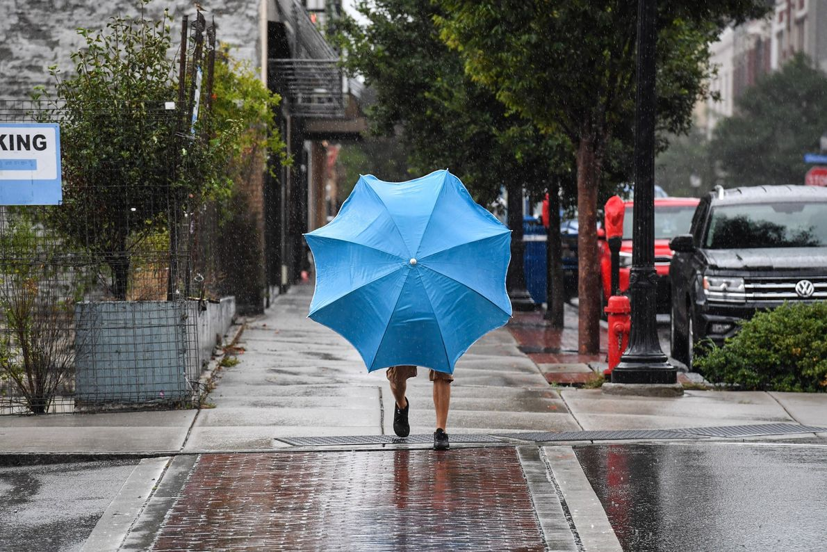 A man uses a beach umbrella to shield himself from the rain the day before Hurricane ...