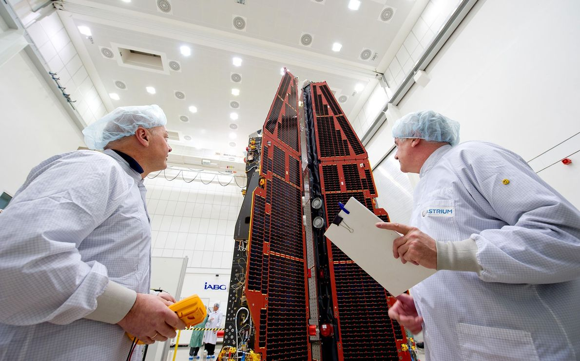 Two IABG employees inspect the ESA environmental satellite 'Swarm' in a clean room in Ottobrunn, Germany. ...