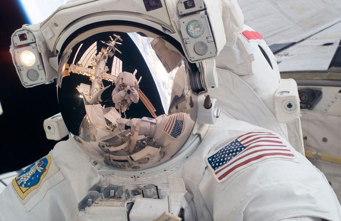 Astronaut Mike Fossum captured this selfie during a spacewalk outside the ISS. His reflection, the space ...