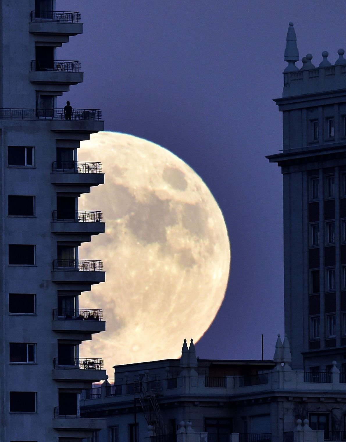 A man stands on a balcony in Madrid as the supermoon rises in November 2016.