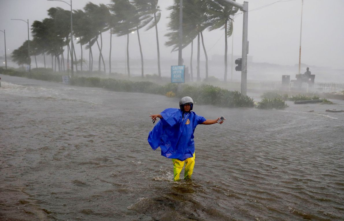 A man directs traffic to avoid a flooded street at the onslaught of Typhoon Mangkhut in ...
