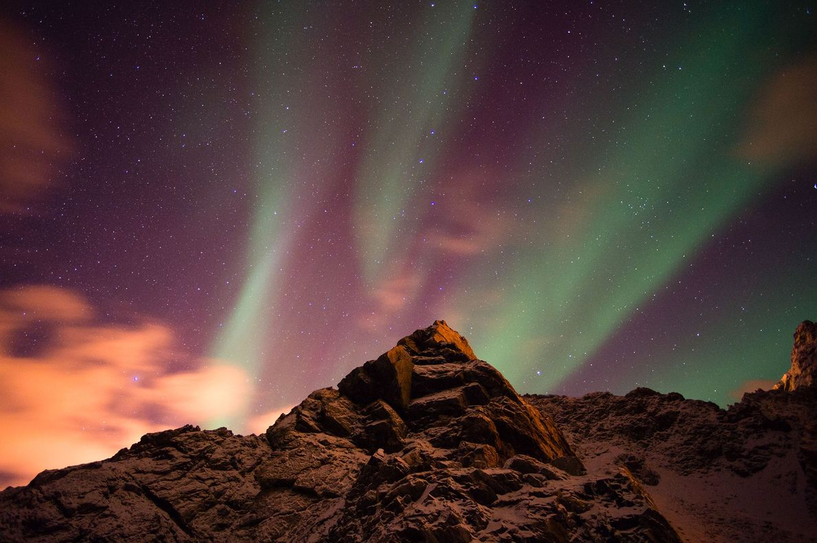 A mountain peak juts into a view of the northern lights from the Vesteralen Islands of ...
