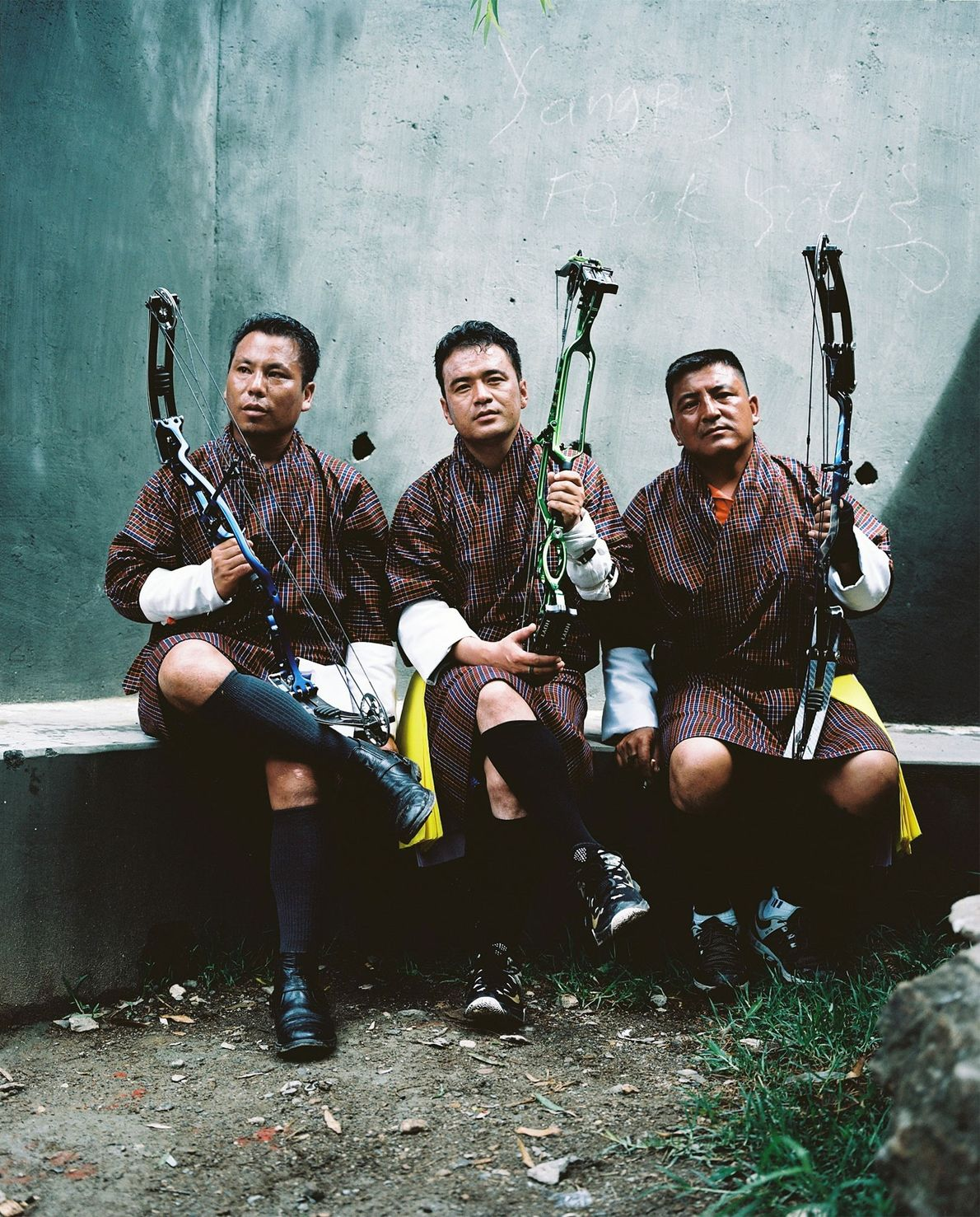 Three men rest during a local archery competition in Paro. From left to right: Pema (his ...
