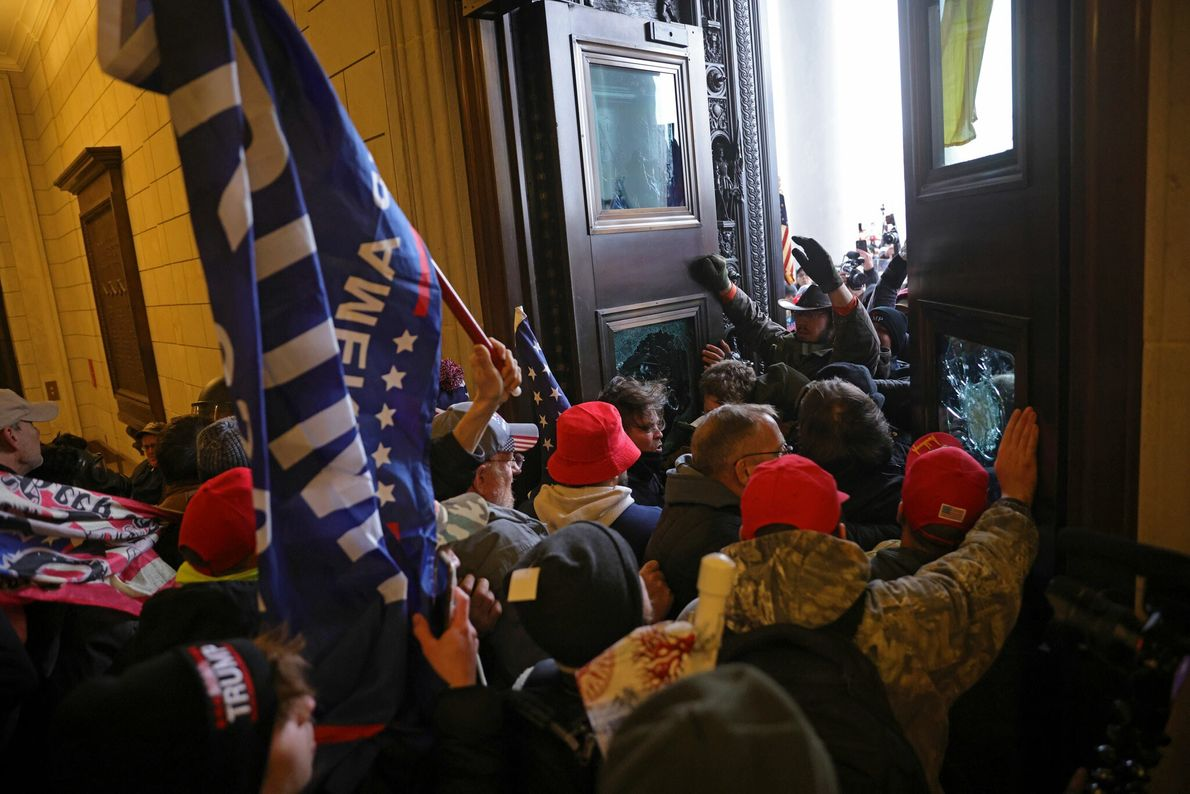 A mob carrying Trump flags and banners stormed through the doors of the U.S. Capitol, swiftly ...