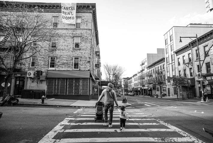 A father walks down Nostrand Avenue in Brooklyn. Above him, a banner calls on New York ...