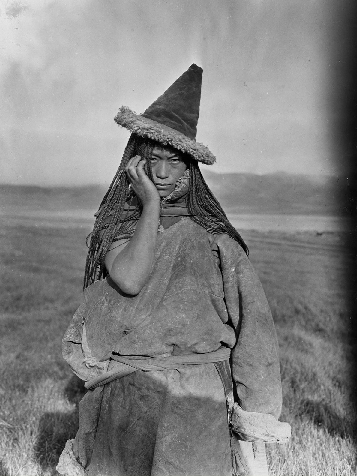 A nomadic Tibetan woman in the People's Republic of China wears a pointed hat made of ...
