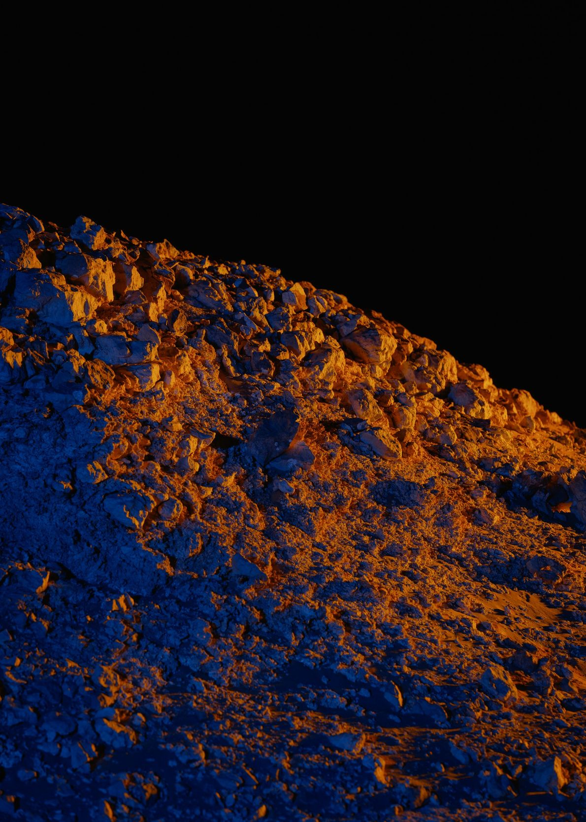 Artificial lighting throws a rocky outcrop north of Kepler Station into stark relief.