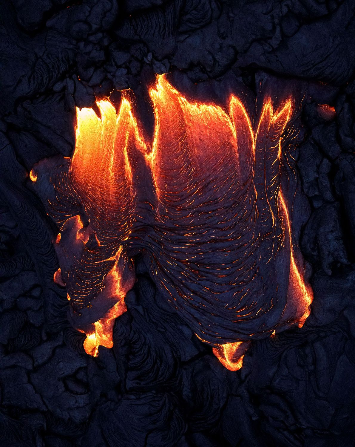 A helicopter shot of lava spurting from rock.