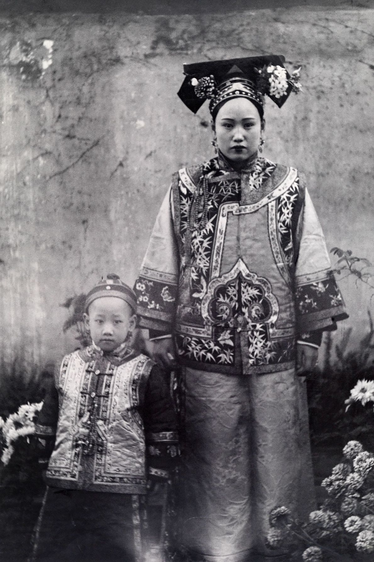 A Chinese mother and her child wear traditional clothing from the Manchurian region of China.