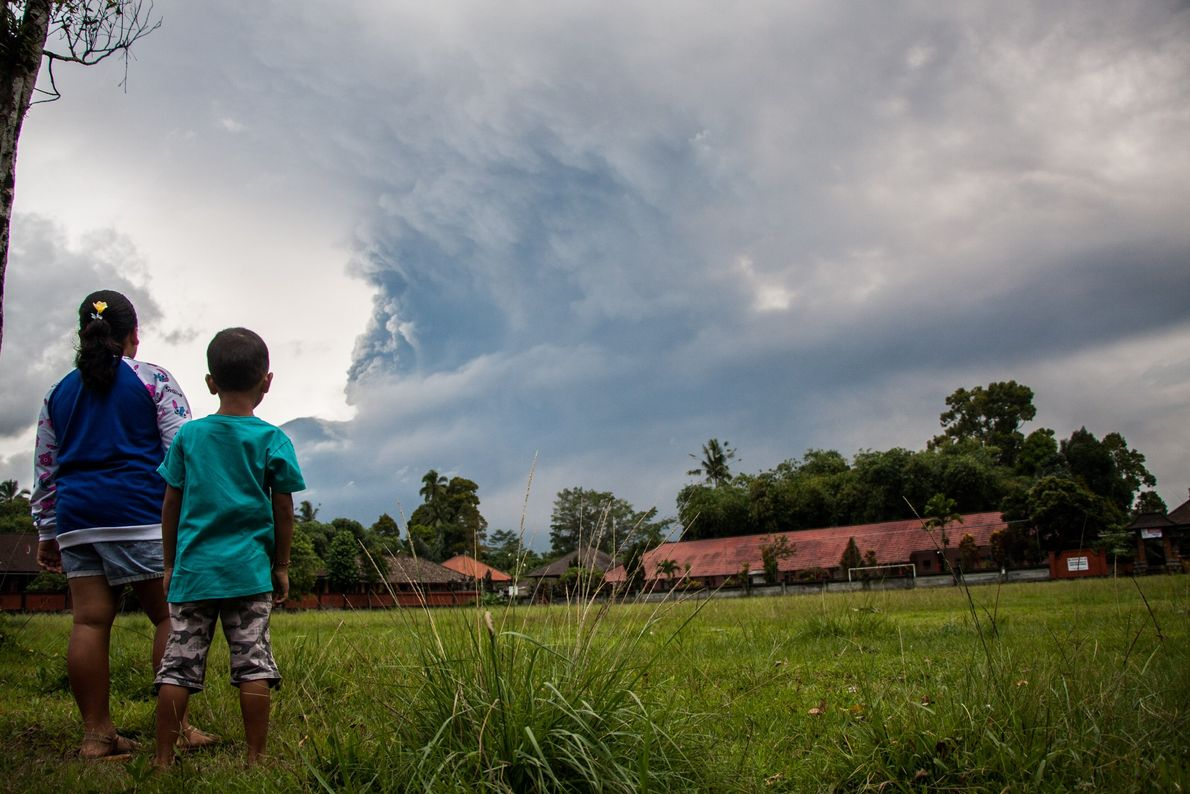 Mount Agung belches smoke as high as 5,000 feet above its summit, sparking an exodus from ...