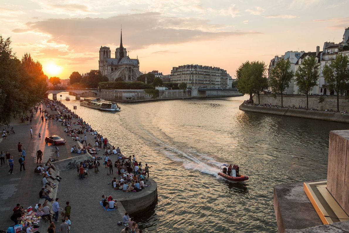 The banks of the Seine are filled with Parisians at sunset.