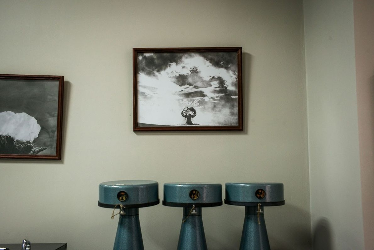 Archive photographs of atomic mushroom clouds are pictured on a wall in the Museum of the ...