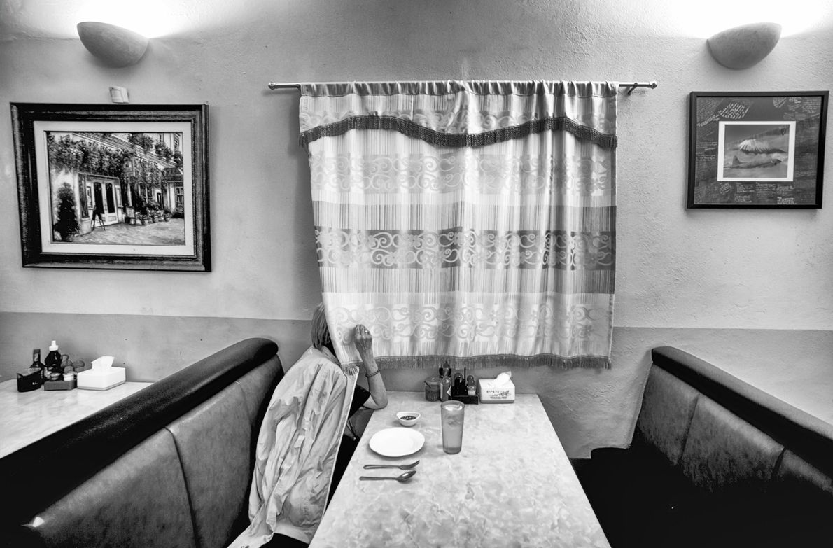 """This restaurant serves Asian ethnic food. While a lone customer waits for her food, she looks ..."