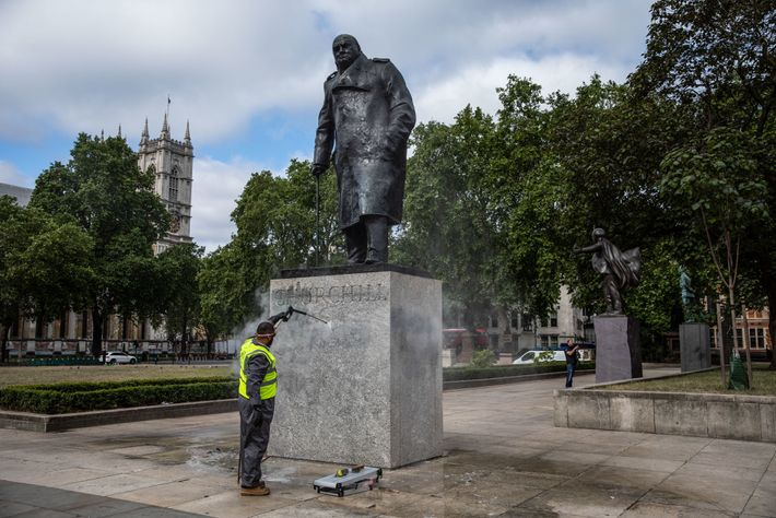 A worker cleans the Winston Churchill statue in London, England's Parliament Square that had been spray ...