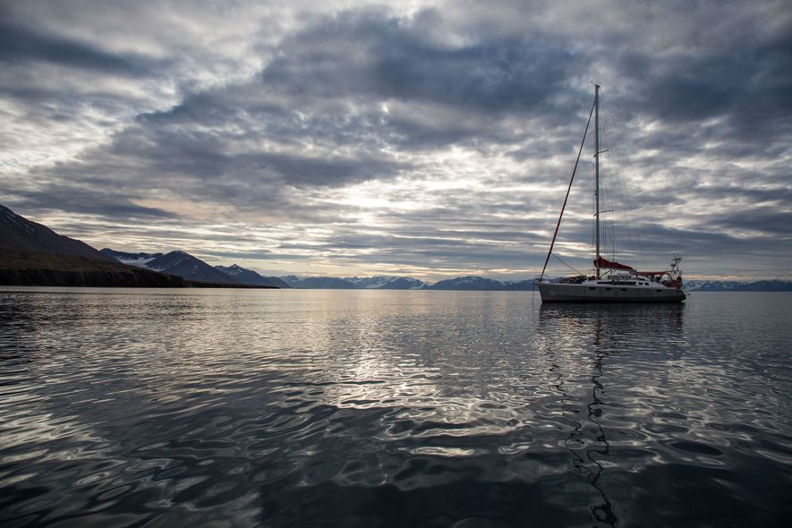 The sailboat sits at anchor on a calm day off the Svalbard archipelago.