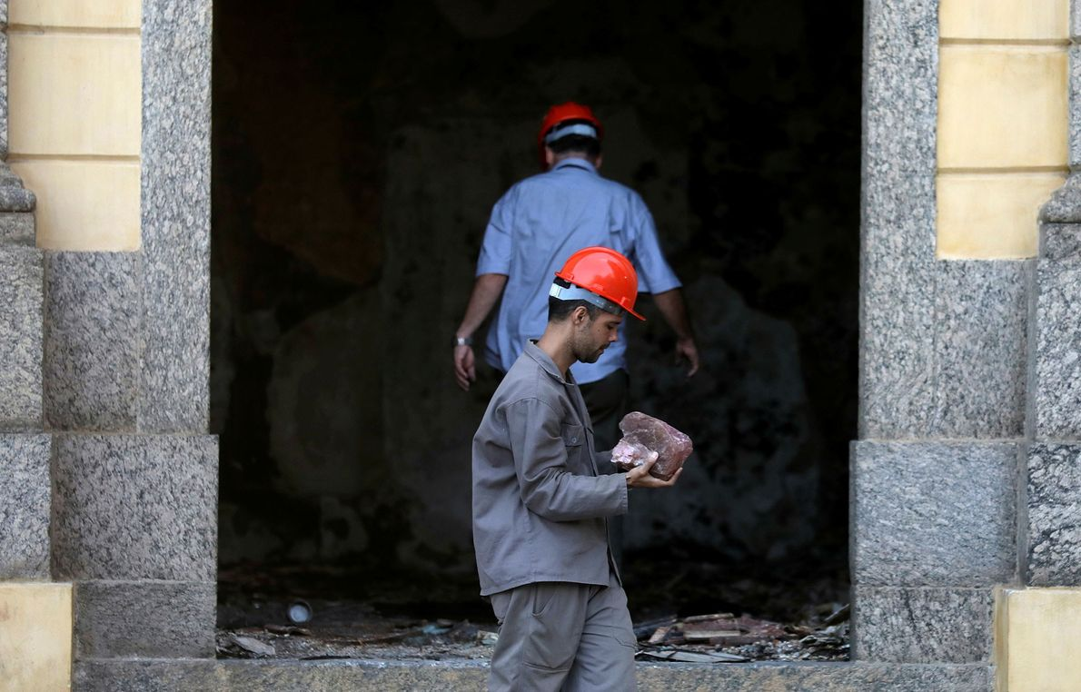 A worker carries a piece of a rock from the National Museum.