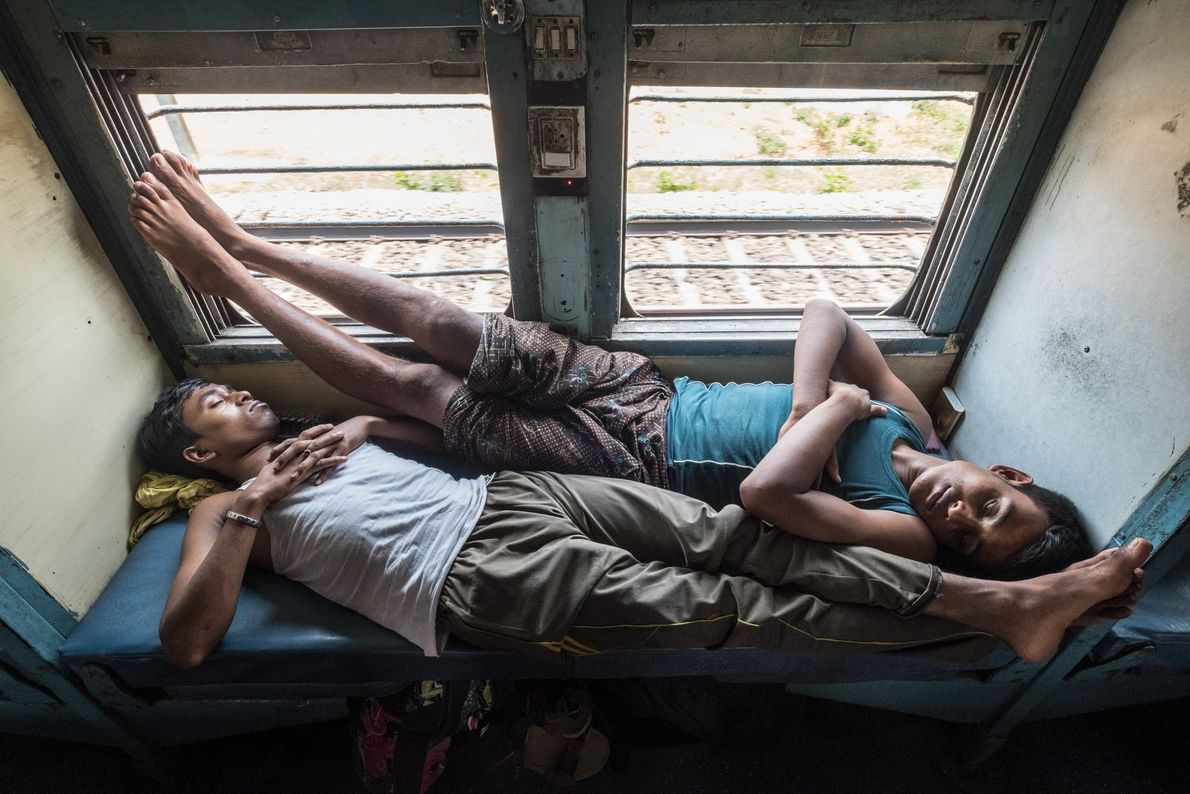 Passengers, mainly construction workers, catch some rest while returning home to northeast India after working in ...