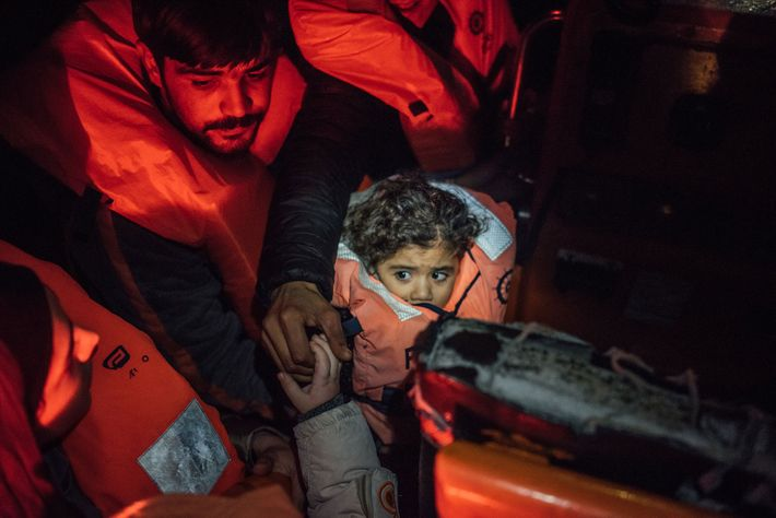 Huddled on the rescue RHIB on their way to the Aquarius, a Syrian child rests in ...
