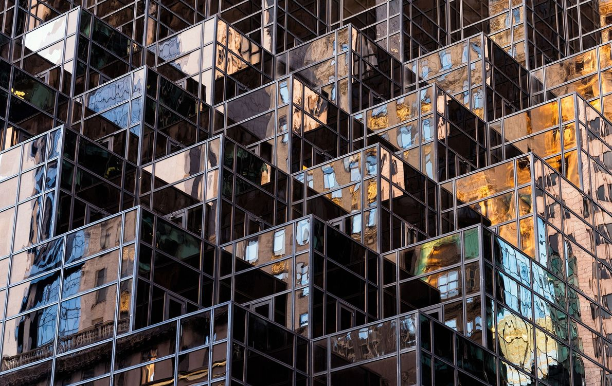 Reflections from late afternoon light dance off a building in Midtown Manhattan. Midtown, one of the ...