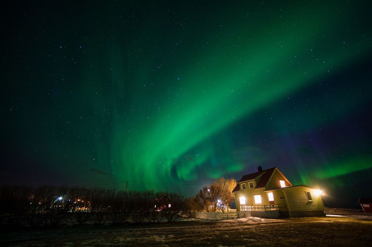 Auroras seem to flow over a house in Nordland, Norway.