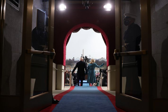 The Bidens walk on a blue-and-red carpet toward the stage on the West Front of the ...