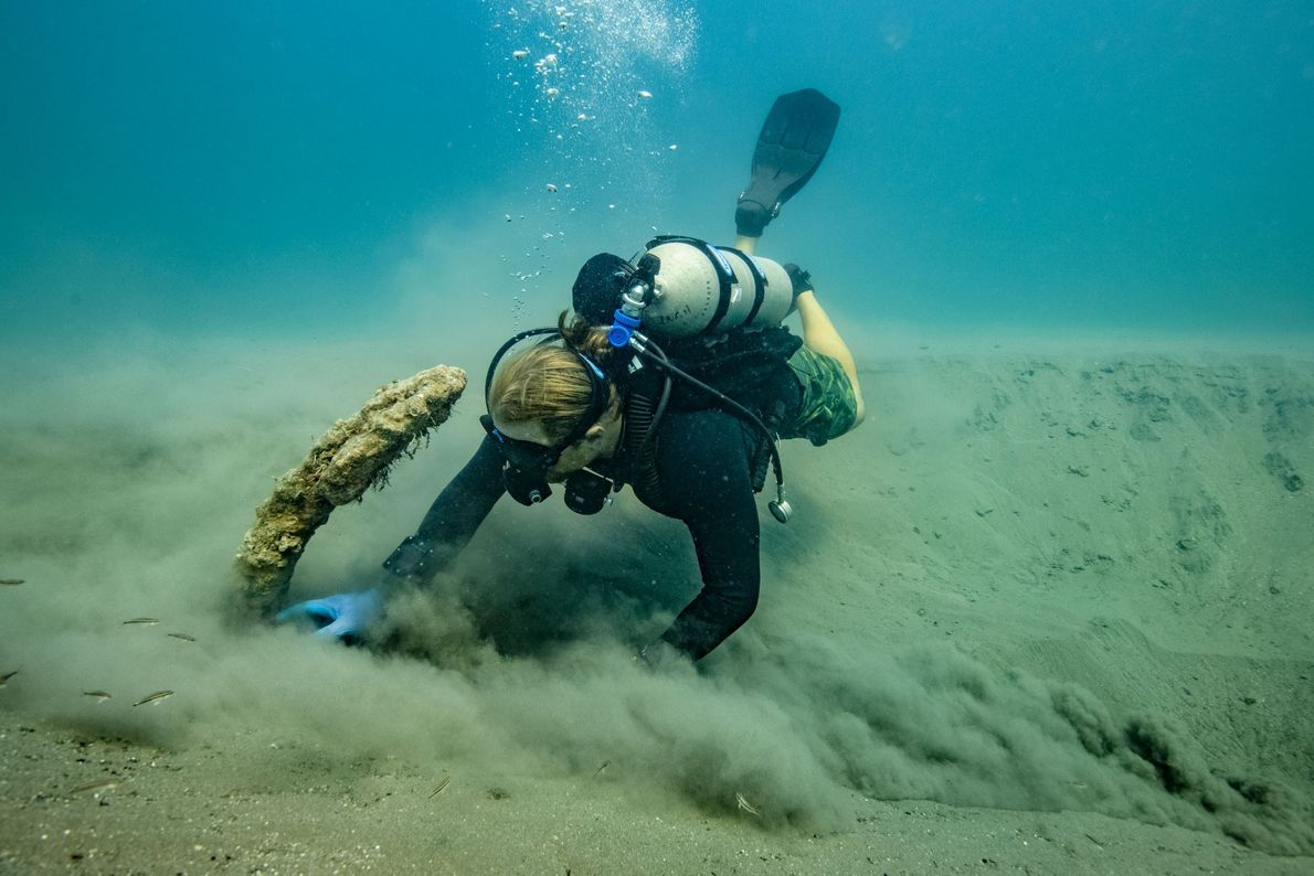 Project co-director Frederick Hanselmann fans sand away from the 16th-century anchor that may have belonged to ...