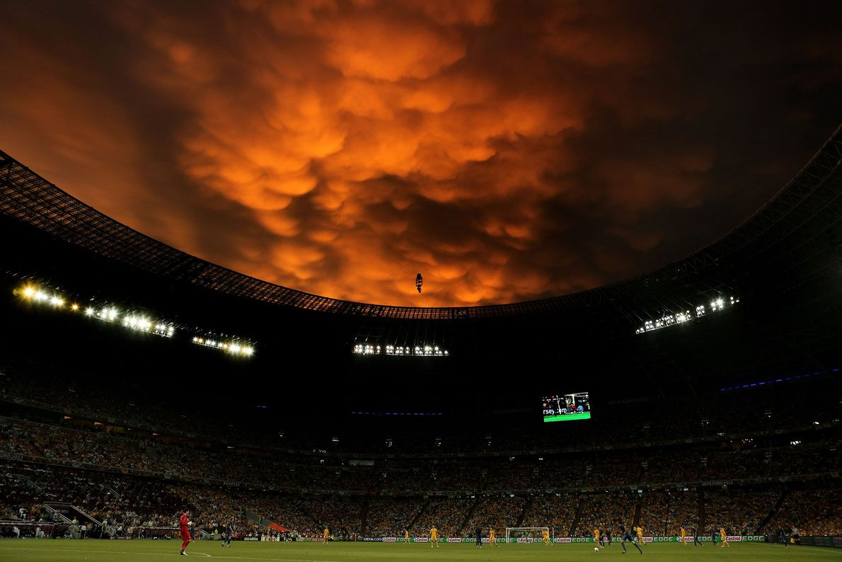 The sunset illuminates clouds over a soccer game in Ukraine.