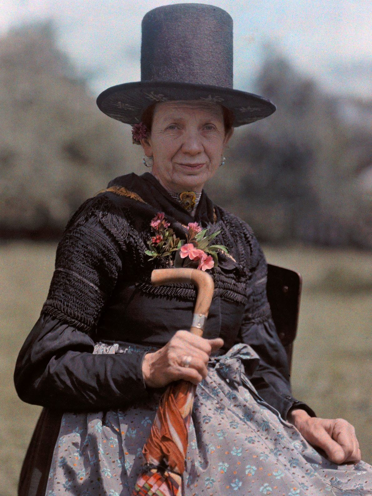 An Austrian woman from Bischofshofen poses in a stovepipe-style hat with embellished features visible below its ...