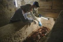 Archaeologists Maysa Rabeeh (left) and Mohammed Refaat (right) examine the degraded wooden coffin of a priest ...