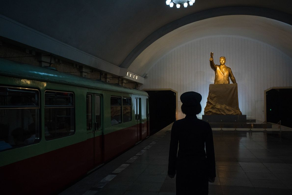 A train station conductor stands before a statue of Kim Il Sung at a Pyongyang subway ...