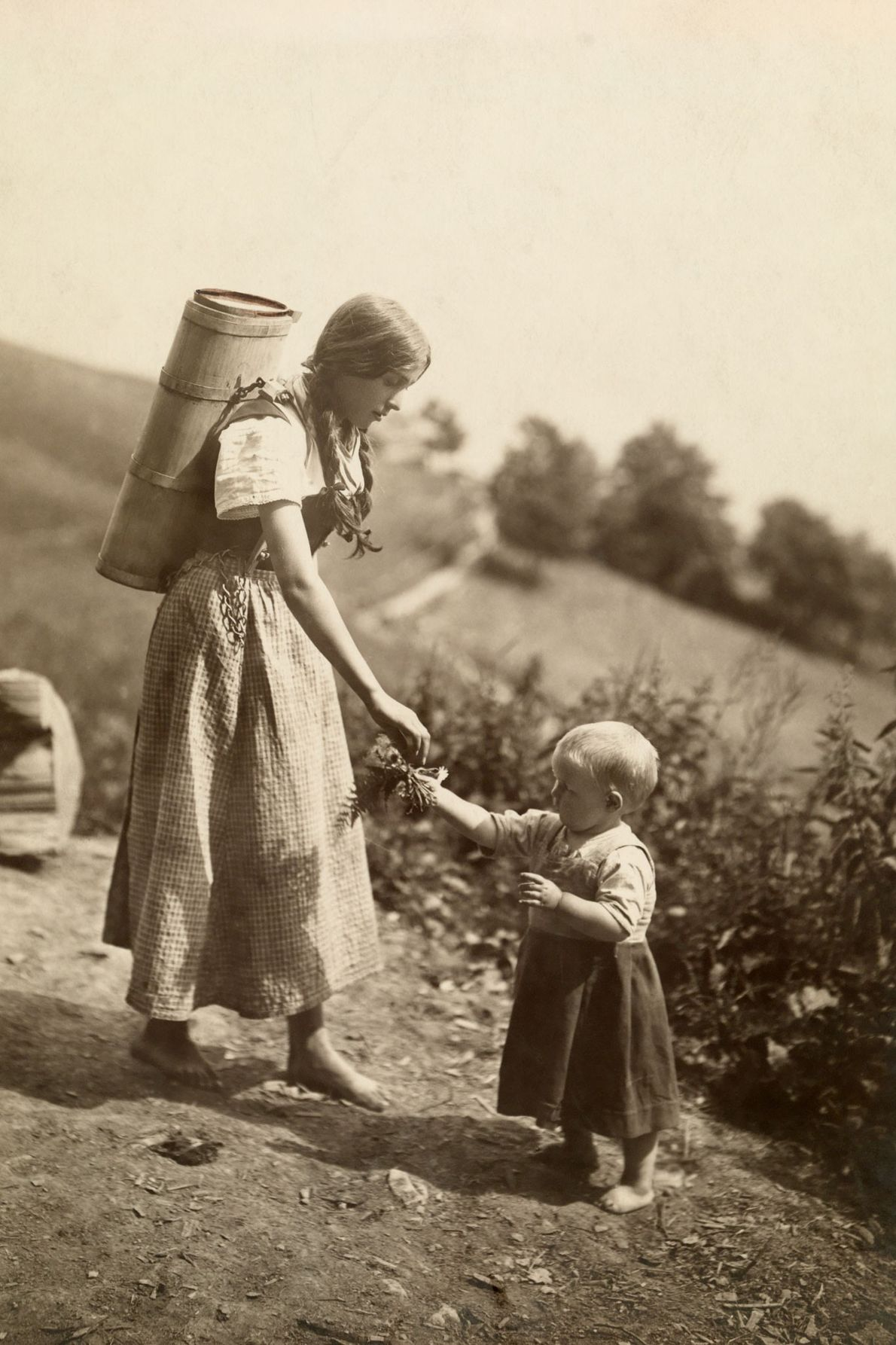 A Swiss mother reaches for her daughter's hand, which is full of flowers.