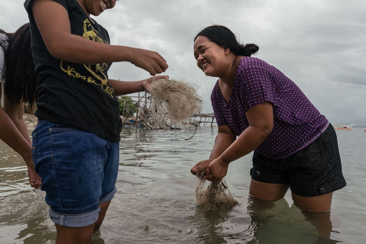 Filipino women clean discarded nets to be sold and recycled abroad.