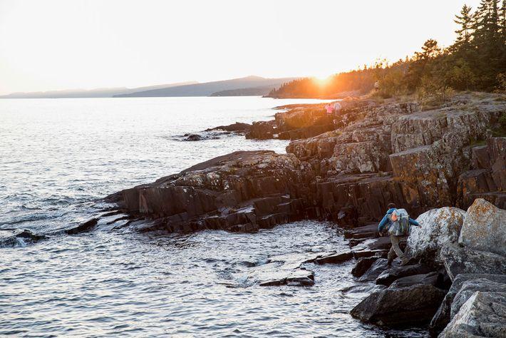 Dupre hikes along the rocky shoreline of Lake Superior.