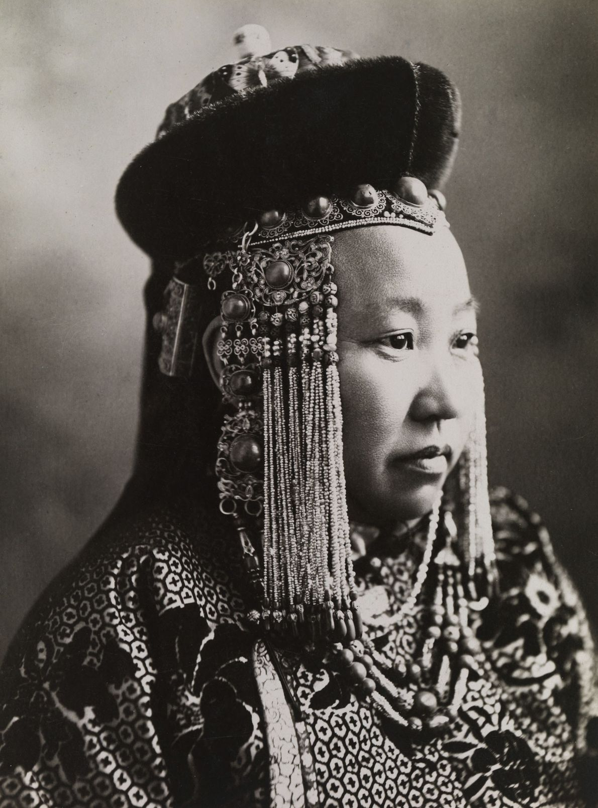 A Mongolian princess wears full court dress, including a traditional headdress.