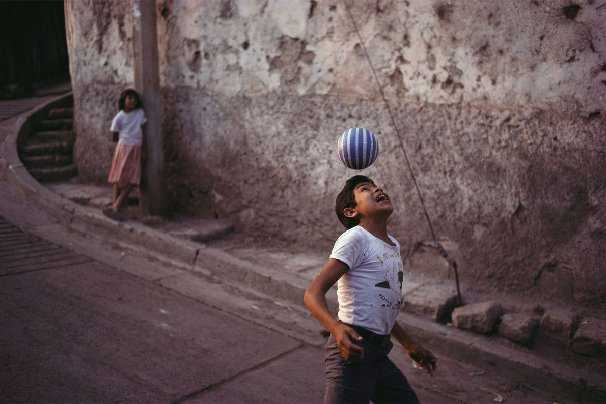 A boy practices his soccer skills along a street in Tegucigalpa, Honduras. The popularity of football ...