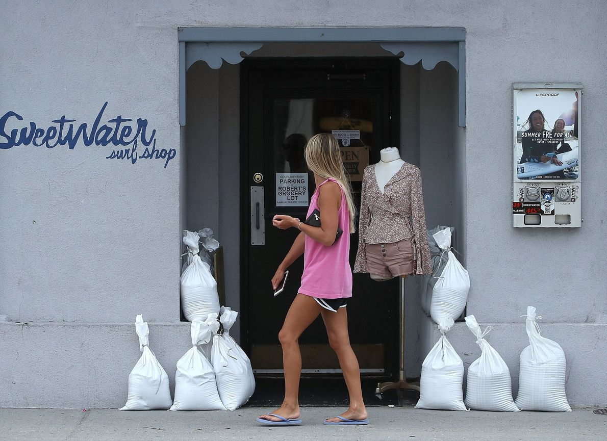 A woman walks past a local shop that braced for the storm earlier this week with ...