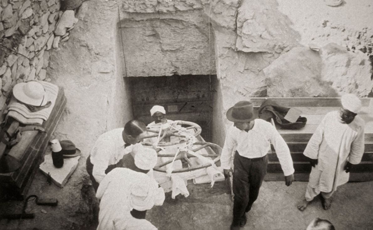 British archaeologist Howard Carter, in the bow tie at left, supervises the removal of two gilded ...
