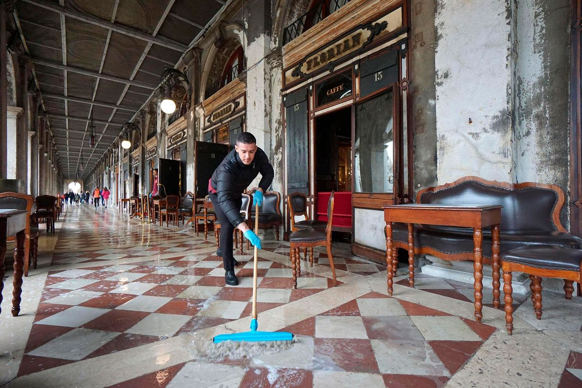 A man brushes away floodwater outside the historic Caffe Florian, in San Marco Square.