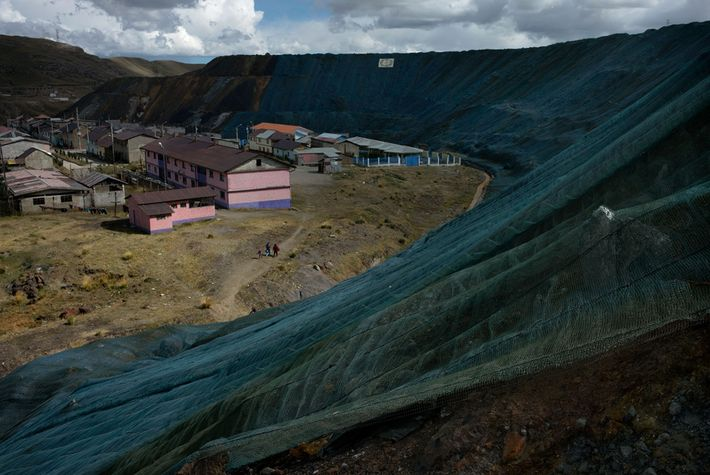 Green mesh placed over tailings piles near the Champamarca neighborhood is meant to reduce the amount ...