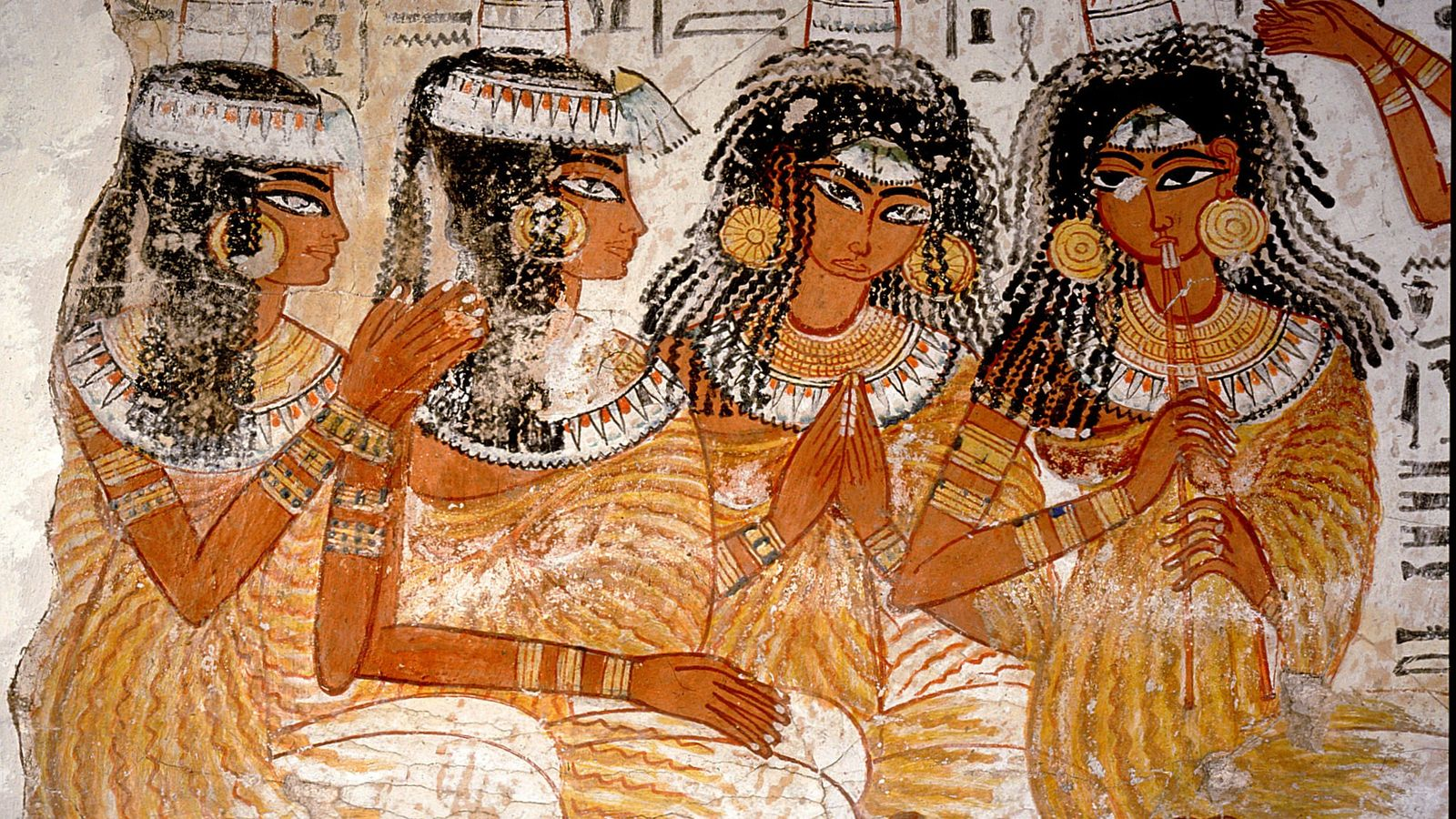 Women in a 3,300-year-old banquet scene are decpicted wearing cone-shaped objects atop their heads. Such depictions ...