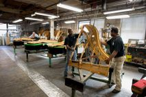 Workers move large piano pieces at the Steinway and Sons factory in Queens, New York.