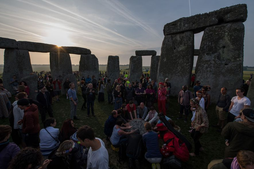 Revellers touch a stone and chant in the stone circle as they celebrate the pagan festival ...