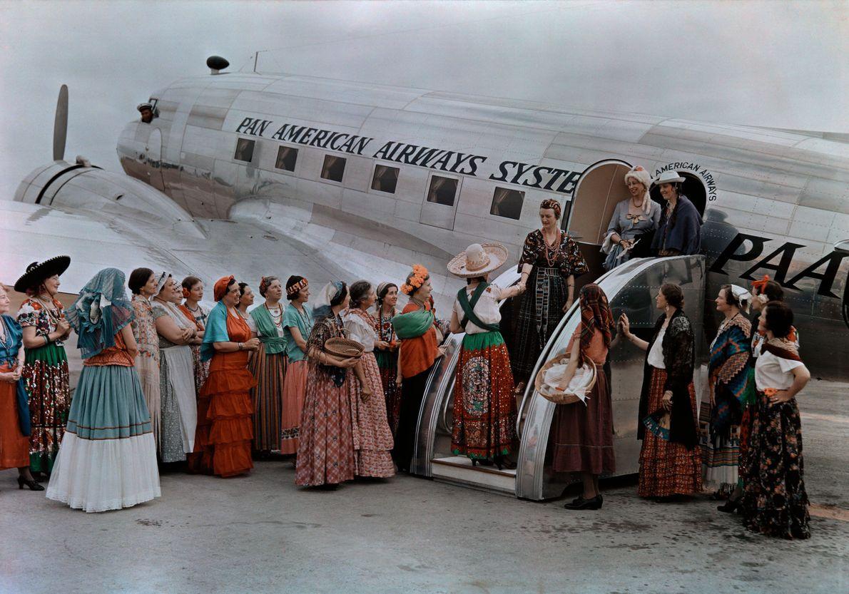 Women in period dress greet women arriving on a Pan Am flight.